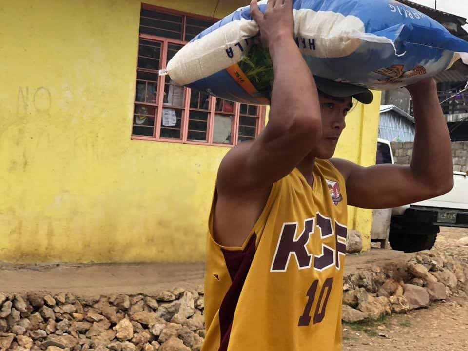 Photo of a man carrying a large bag of rice on his head.