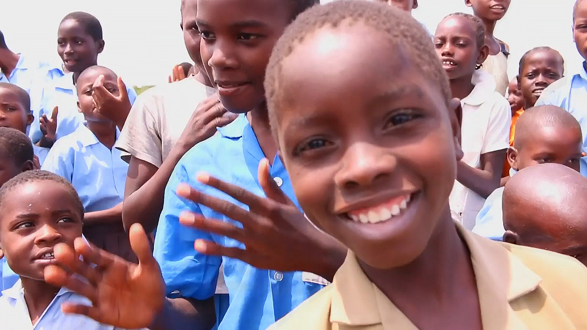 A smiling child in front of a group of friends.