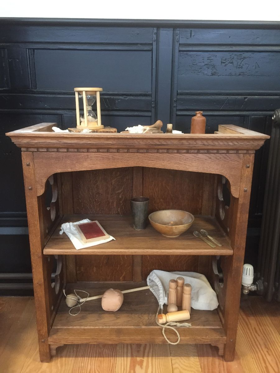 Bookcase displaying replica artefacts from a Tudor schoolroom.